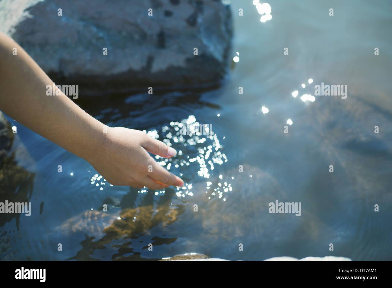 Une jeune fille se pencher en avant pour mettre sa main dans l'eau claire du lac peu profond, New York USA Ashokan approvisionne U S Photo Stock