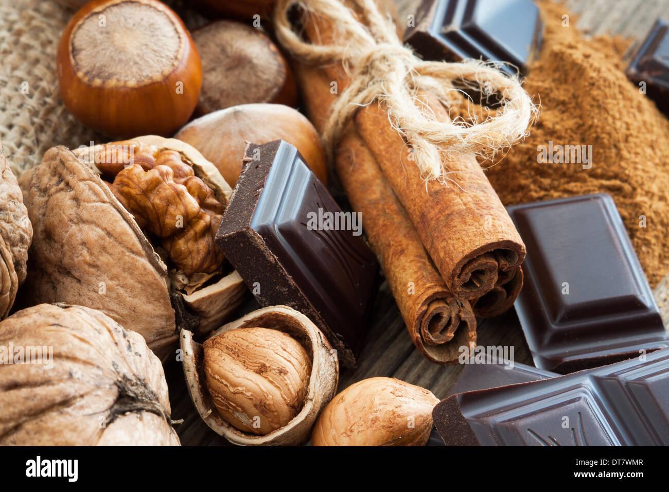 Noisettes, noix mûres, des bâtons de cannelle et chocolat Photo Stock