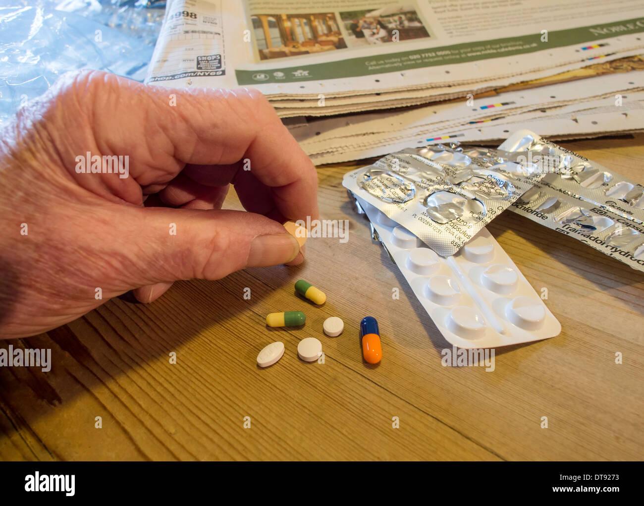 La main de l'homme âgée avec sélection de comprimés, comprimés et gélules. Dose quotidienne de médicaments. Photo Stock