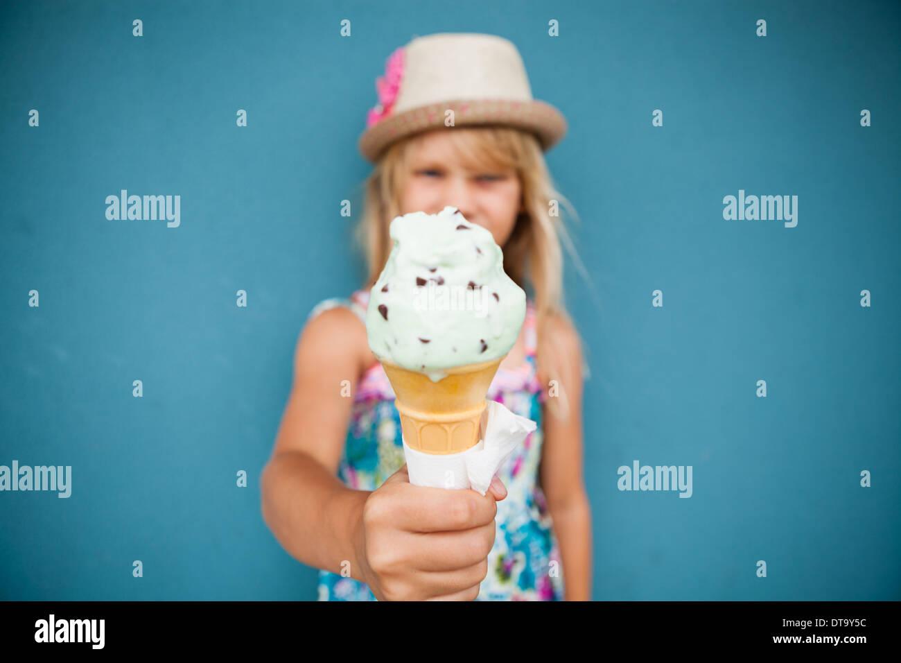 Libre et l'accent sur glace vanille cône maintenu par cute young girl Photo Stock