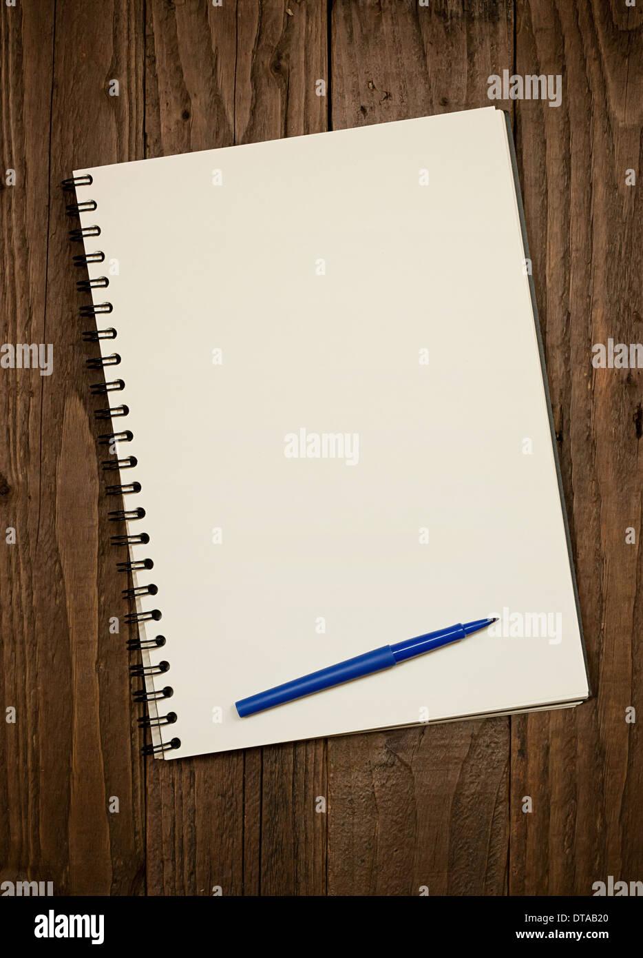 Album à spirale en blanc sur un fond en bois rustique avec copie espace et stylo à pied du pad. Photo Stock