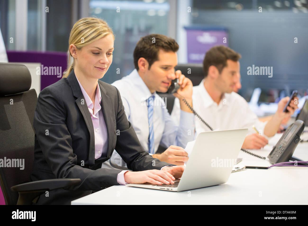 Les activités axées sur le travail d'équipe au bureau avec ordinateur et téléphones portables Banque D'Images