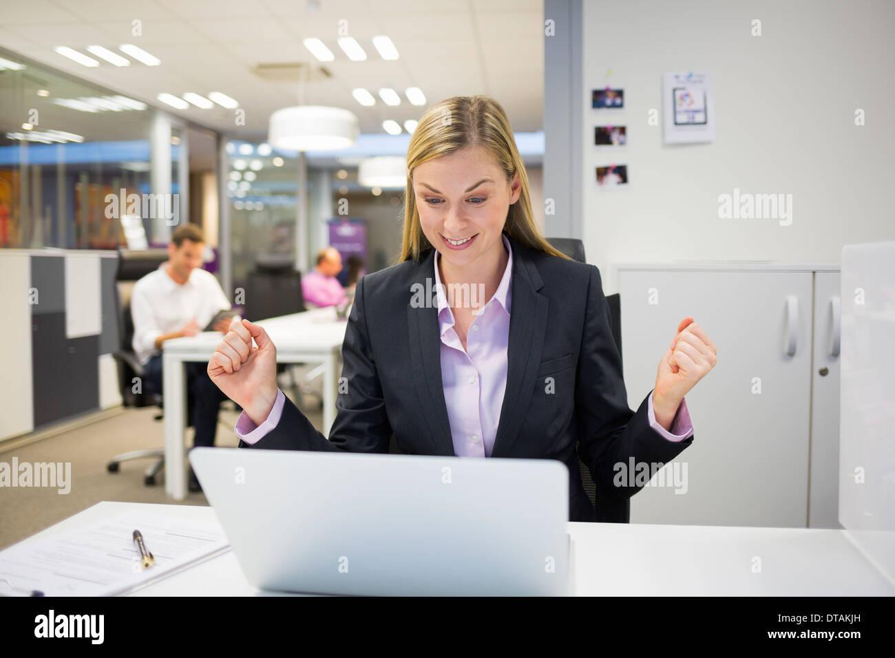 Succès businesswoman with arms jusqu'au bureau Photo Stock