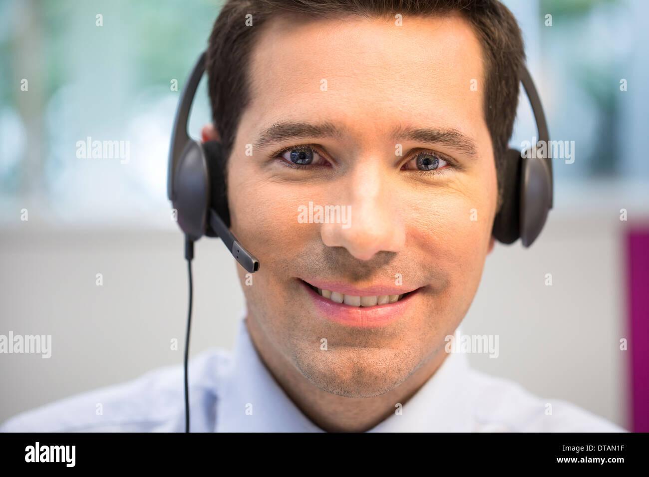 Portrait of businessman in office sur votre téléphone avec casque, à huis clos Photo Stock