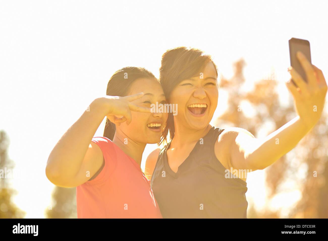 Deux jeunes femmes faire Self Portrait in park Photo Stock