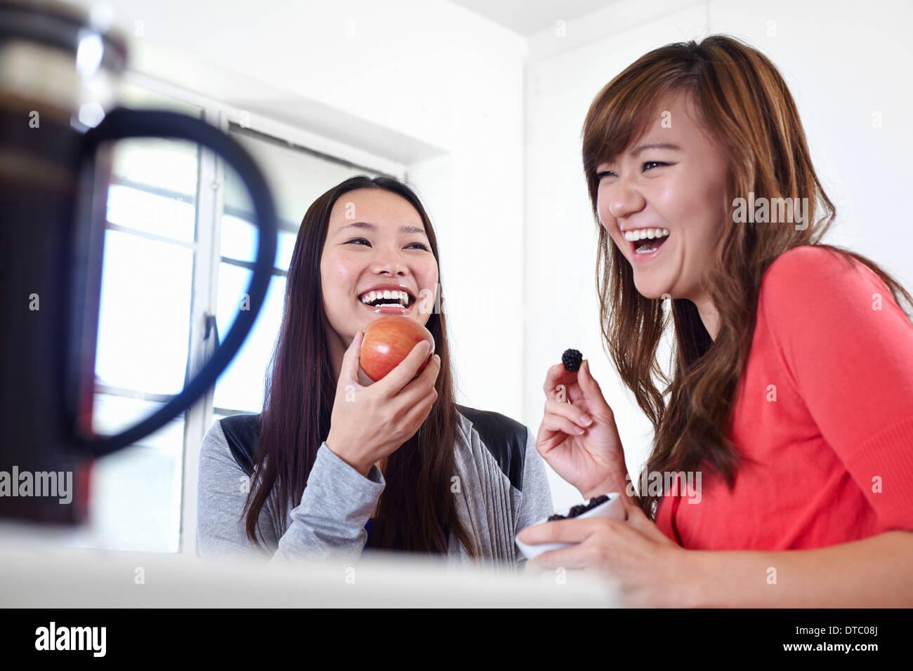 Deux jeunes femmes dans la cuisine manger des fruits Banque D'Images