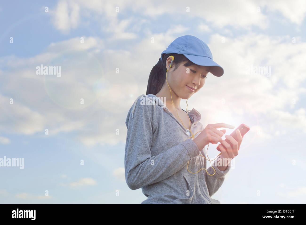 Young female runner le choix de la musique à partir de MP3player Photo Stock
