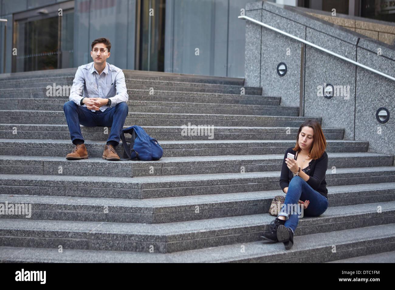 Malheureux couple sitting on steps apart Photo Stock