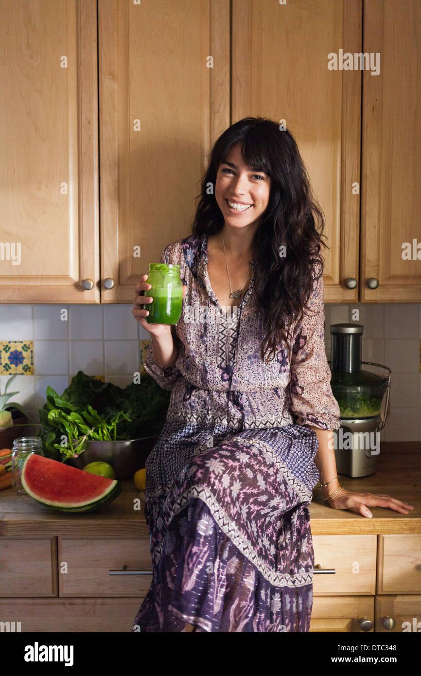 Jeune femme en cuisine avec du jus de légumes Photo Stock