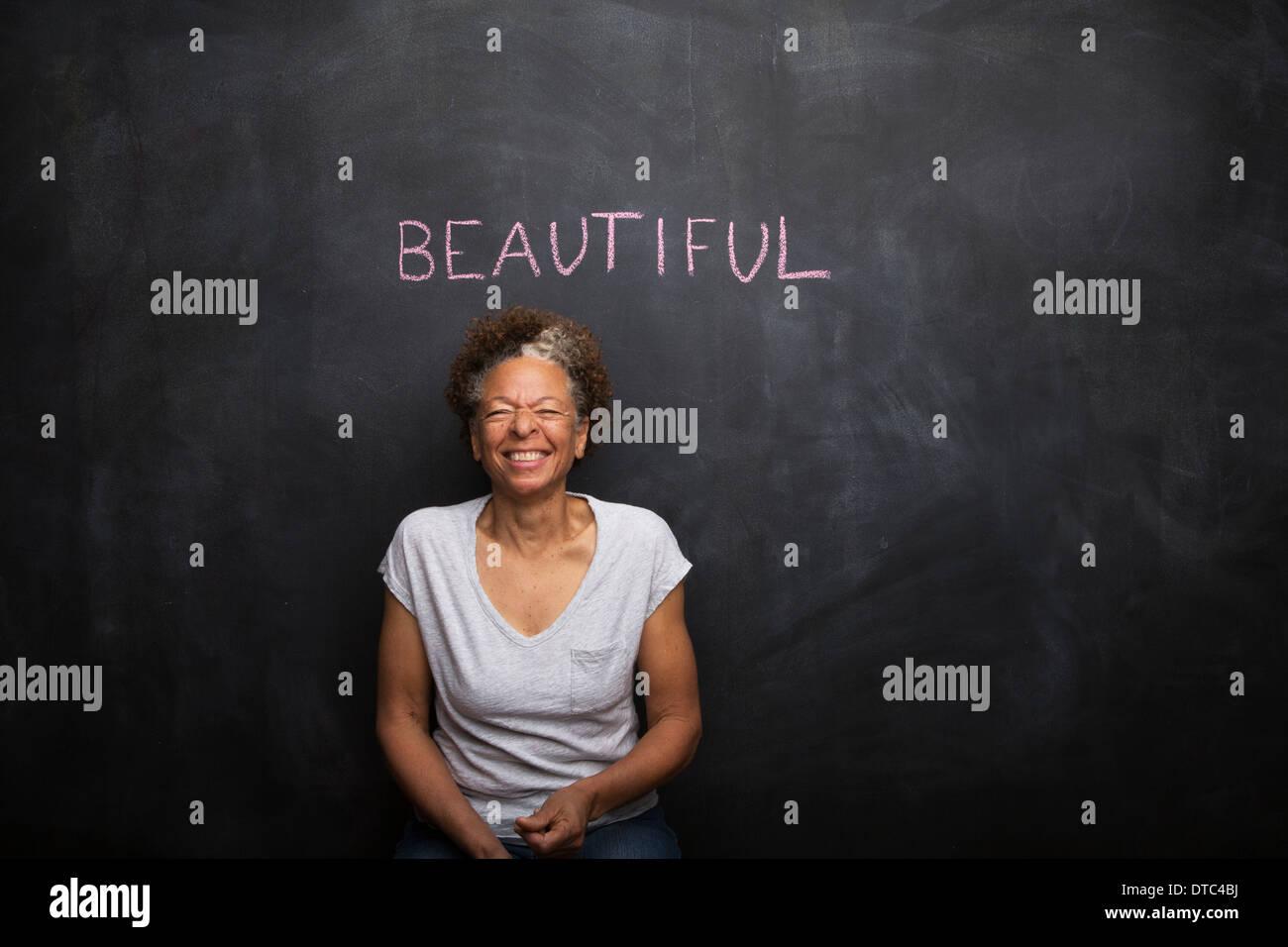 Senior woman in front of blackboard et le mot belle Photo Stock
