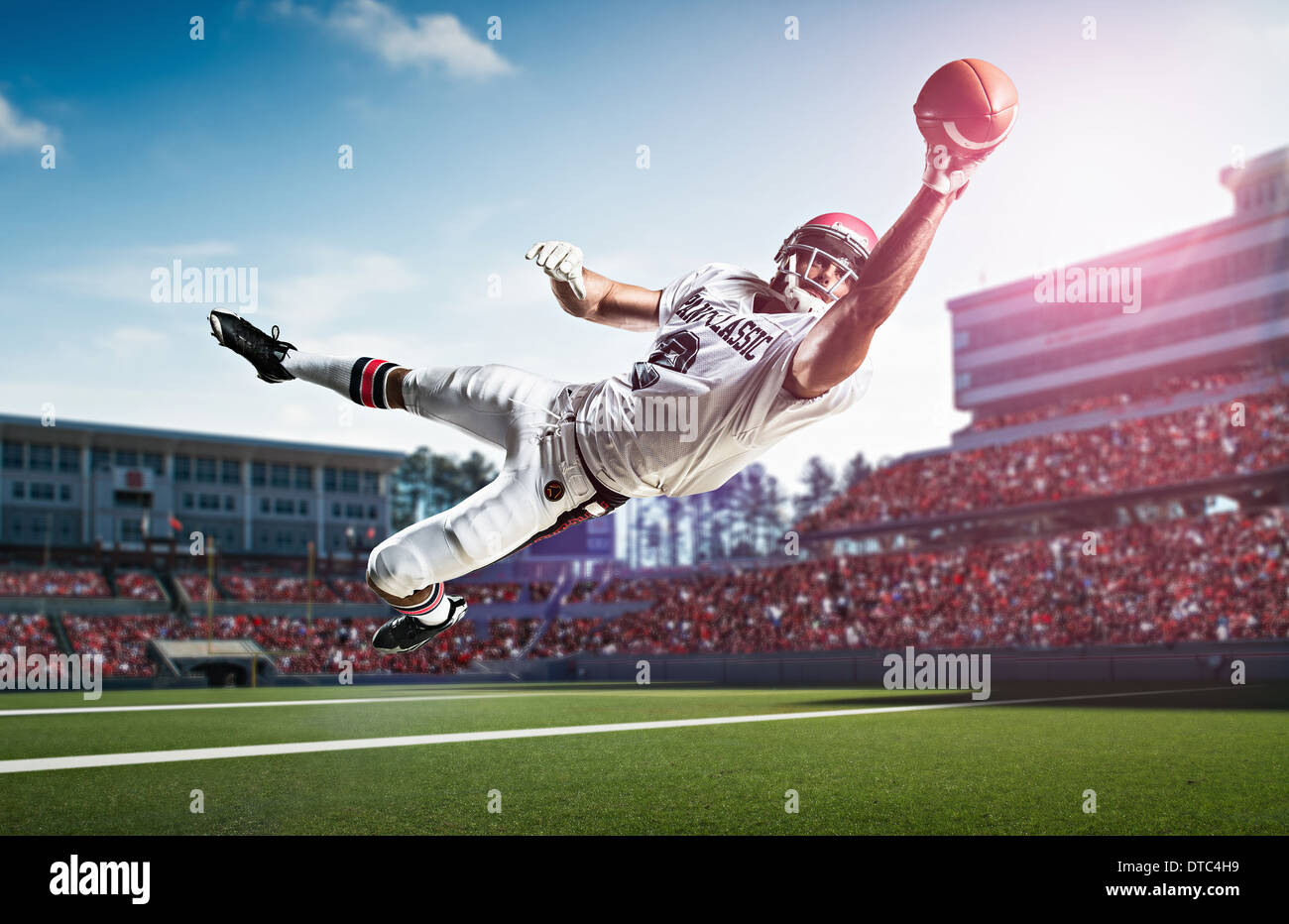 American football player catching ball mid air dans le stade Photo Stock