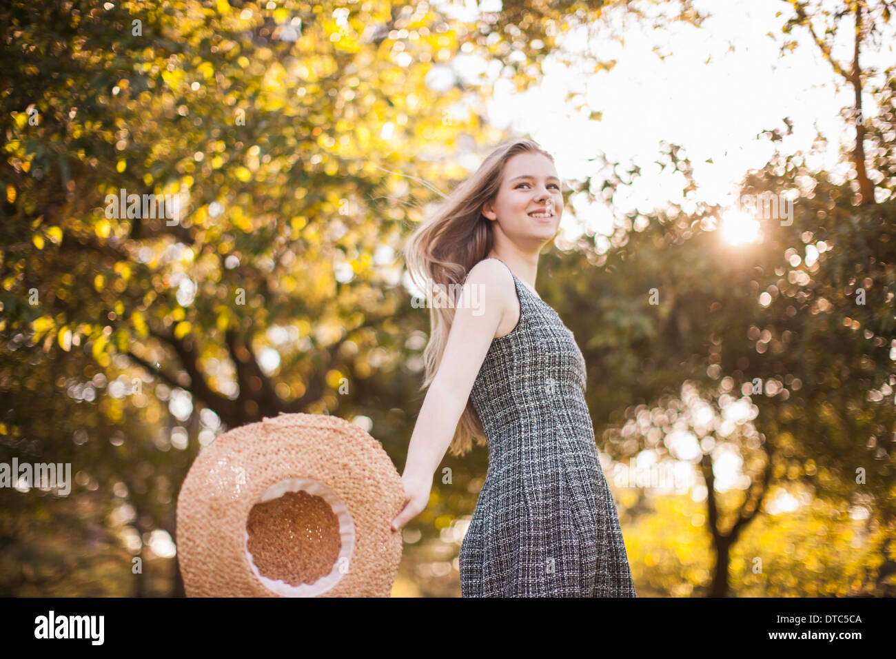Teenage girl holding chapeau running in park Banque D'Images