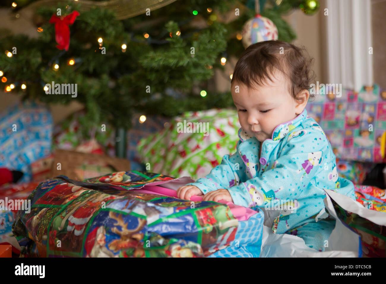Baby Girl ouverture présente sur son premier Noël Photo Stock