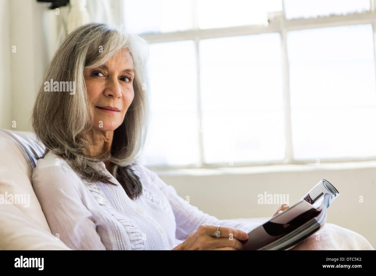Portrait of attractive senior woman reading magazine Photo Stock