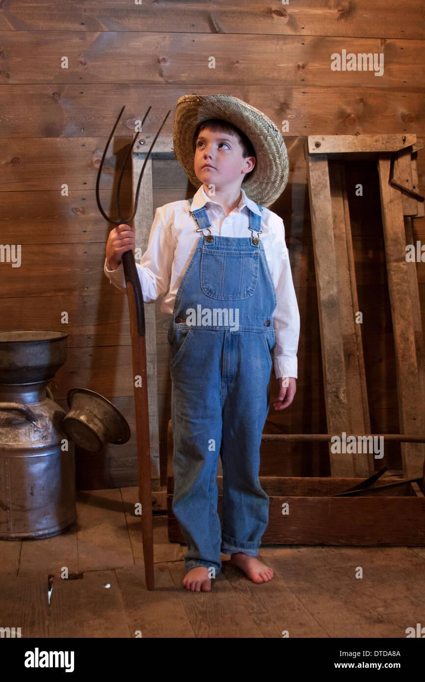 Un jeune agriculteur garçon tenant une fourche Photo Stock