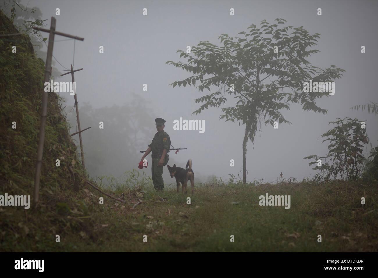 Une KIA soldat vérifier un chemin qui mène à la Naw Hpyu poster dans la ligne de front de la guerre contre le Gouvernement de la Birmanie Banque D'Images