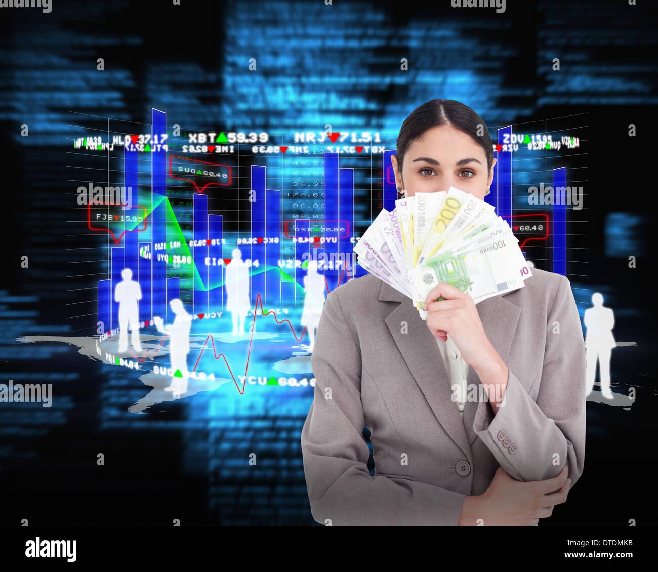 Composite image of young businesswoman cachant son visage derrière des billets de banque Banque D'Images