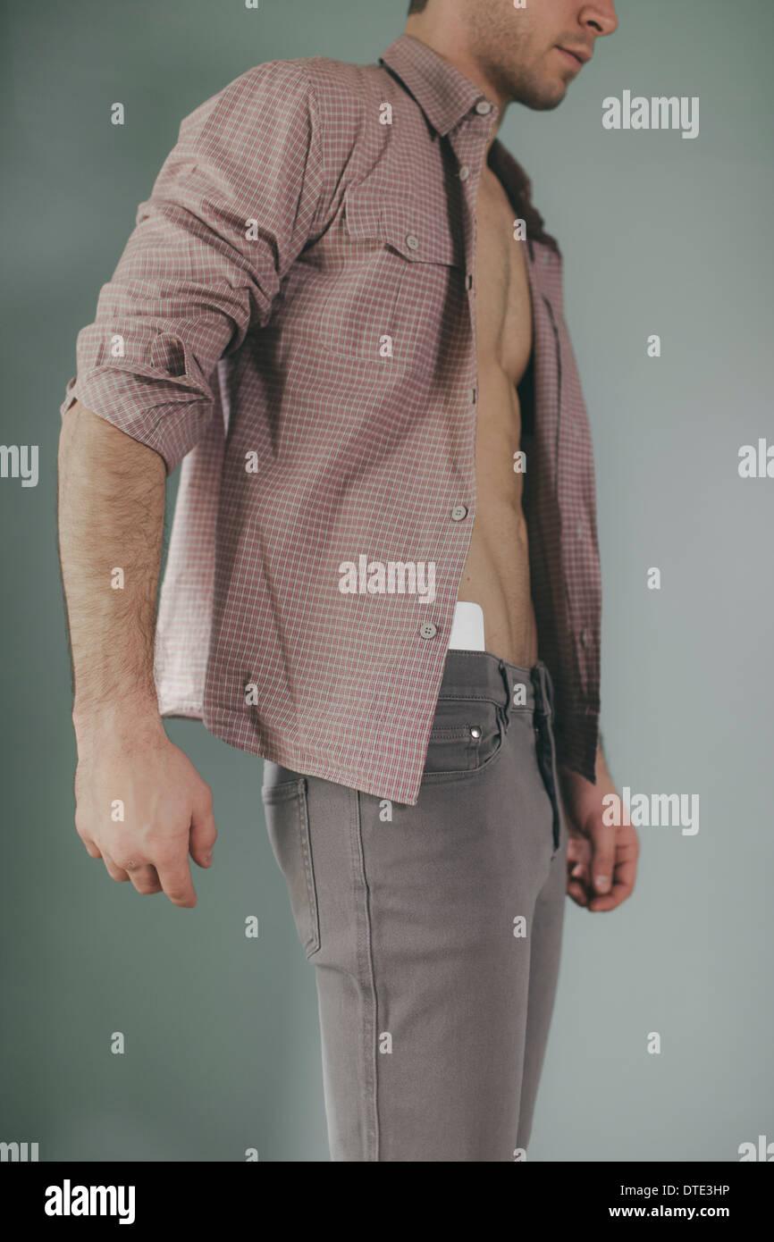 Partie d'une série montrant différentes façons on est porteur d'un smartphone, nichée dans la taille des jeans serrés. Photo Stock