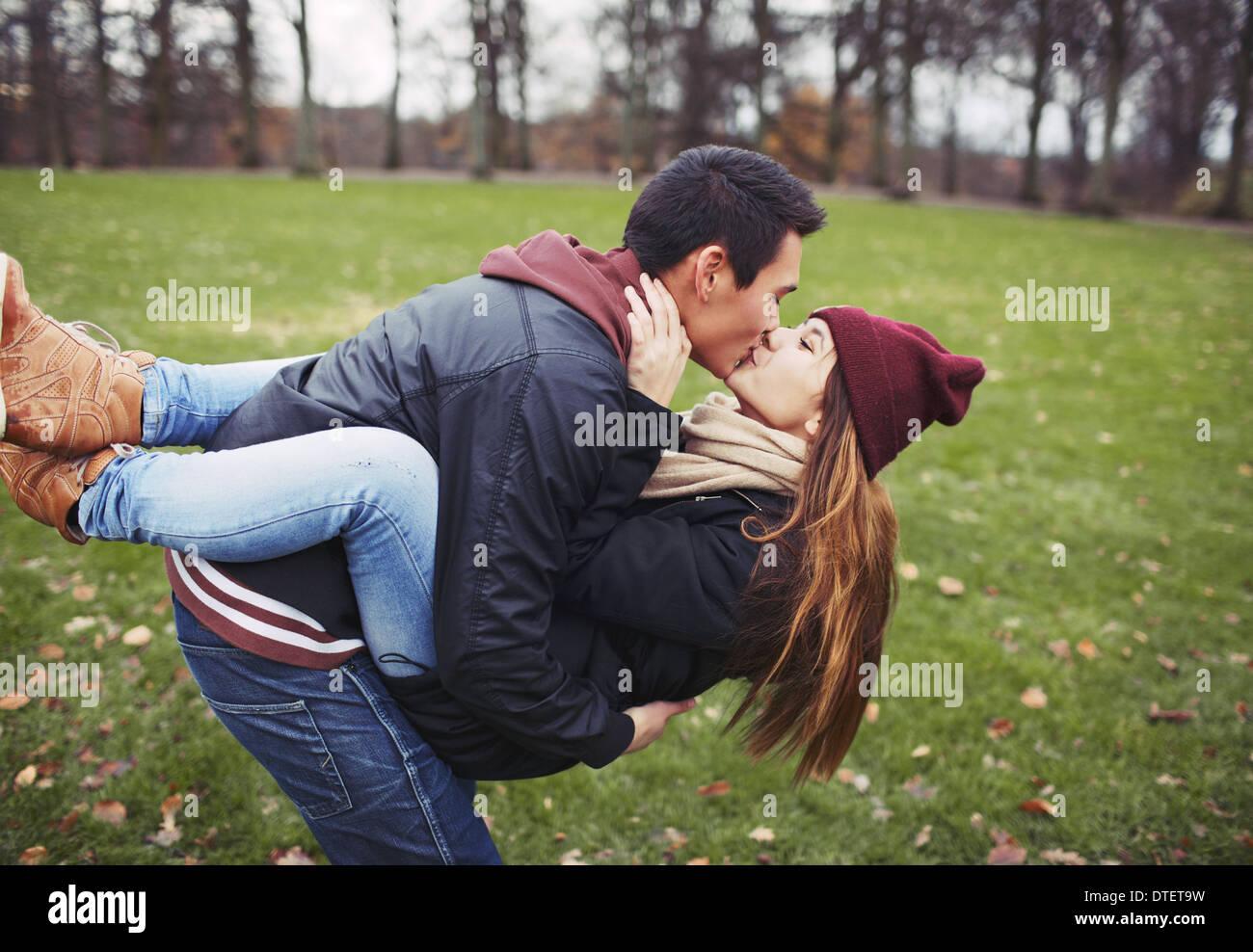 Beau jeune homme portant sa jolie petite amie et s'embrasser. Mixed Race couple dans l'amour en plein air dans le parc. Photo Stock