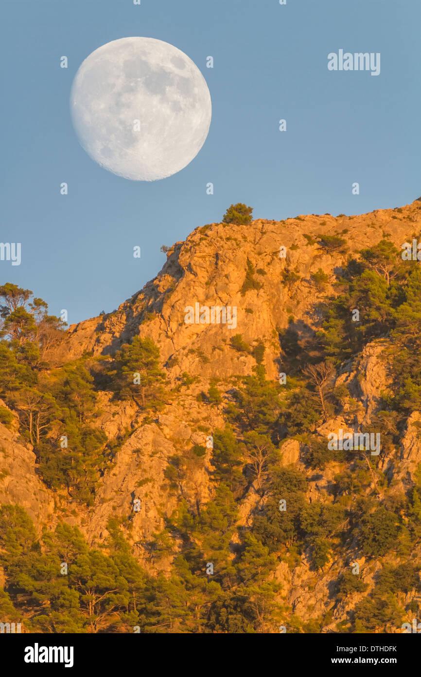 Du vrai pleine lune croissante au Puig des Teix mountain au coucher du soleil. Montagnes de Tramuntana, Deià, Majorque, îles Baléares, Espagne Banque D'Images