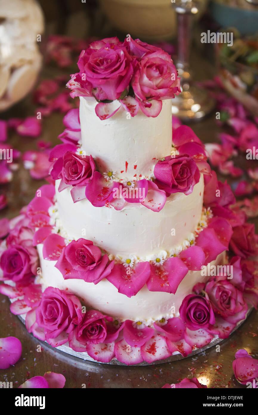 Un gâteau de mariage à trois niveaux couverts en glaçage blanc et décoré avec des pétales de rose en Angleterre Photo Stock