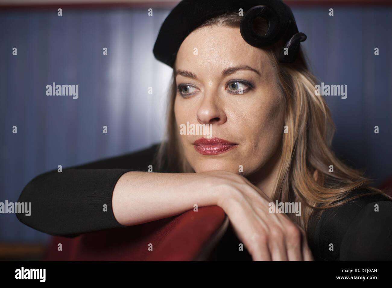 Une femme dans un théâtre portant un chapeau noir et soirée de repos haut son menton sur sa main à l'écart dans Banque D'Images