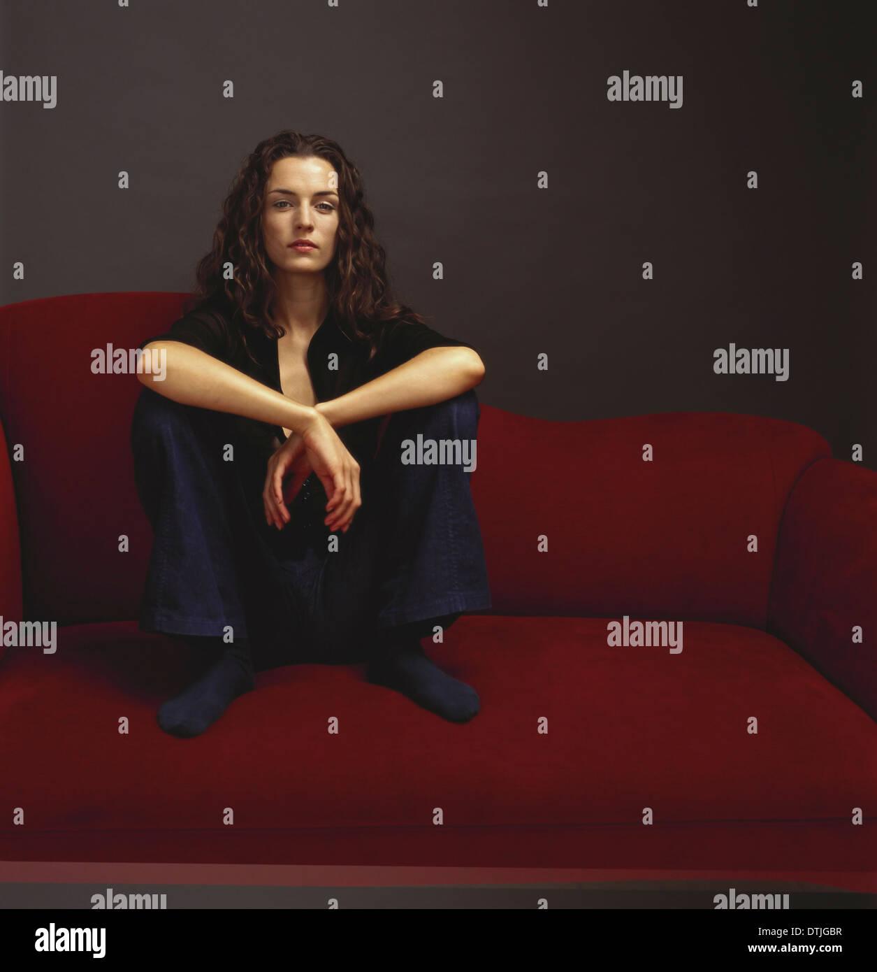 Une femme vêtue de noir assise sur un canapé rouge Cape Town Afrique du Sud Banque D'Images