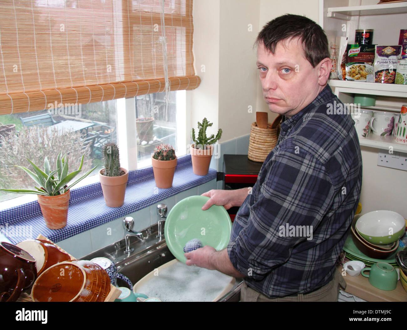Man washing up pots avec peu d'enthousiasme à un évier de cuisine à la maison, England, UK Banque D'Images