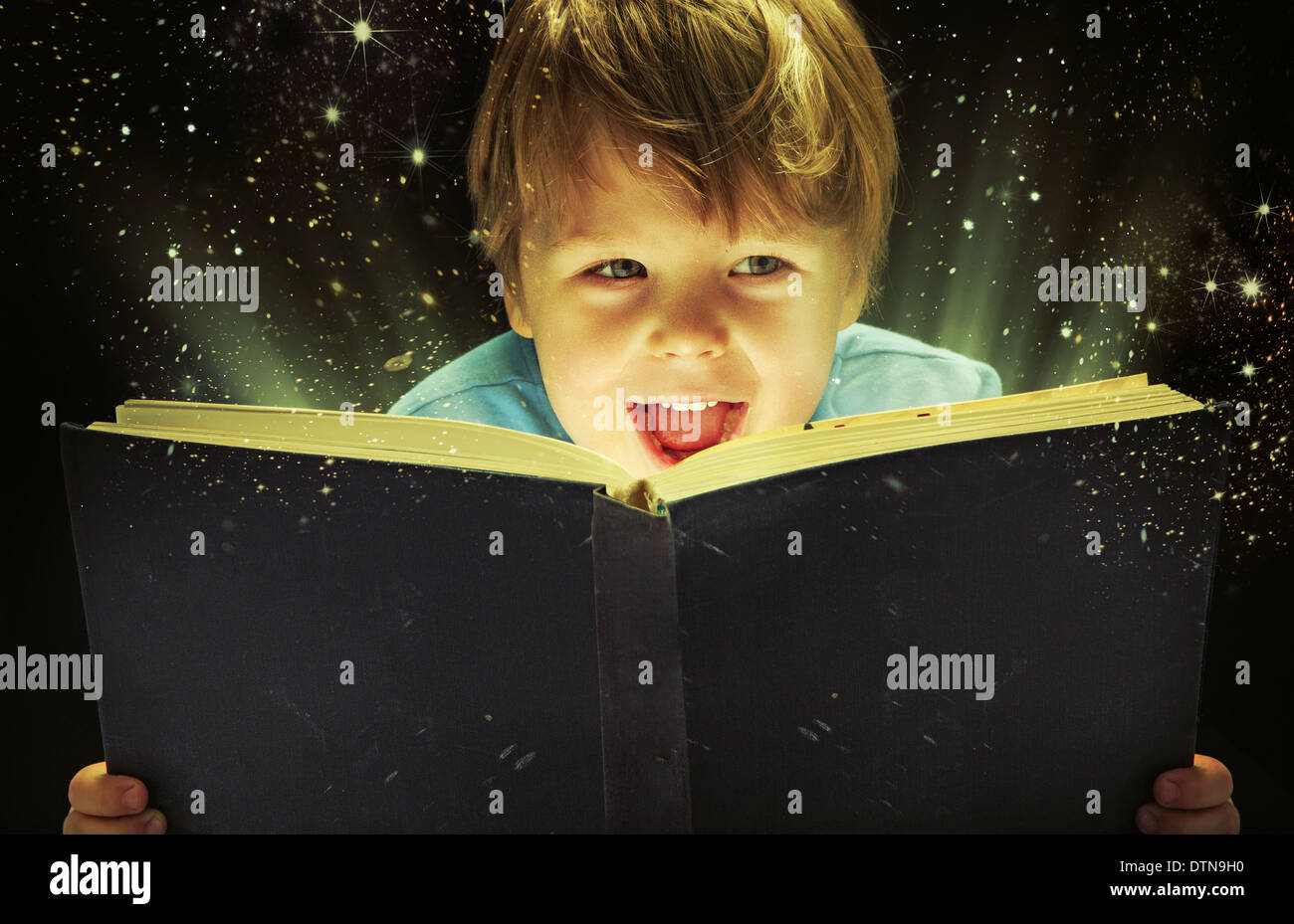 Petit garçon portant un vieux livre de magie Photo Stock