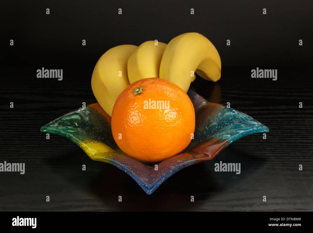 La banane et l'orange dans un bol en verre de couleur Photo Stock