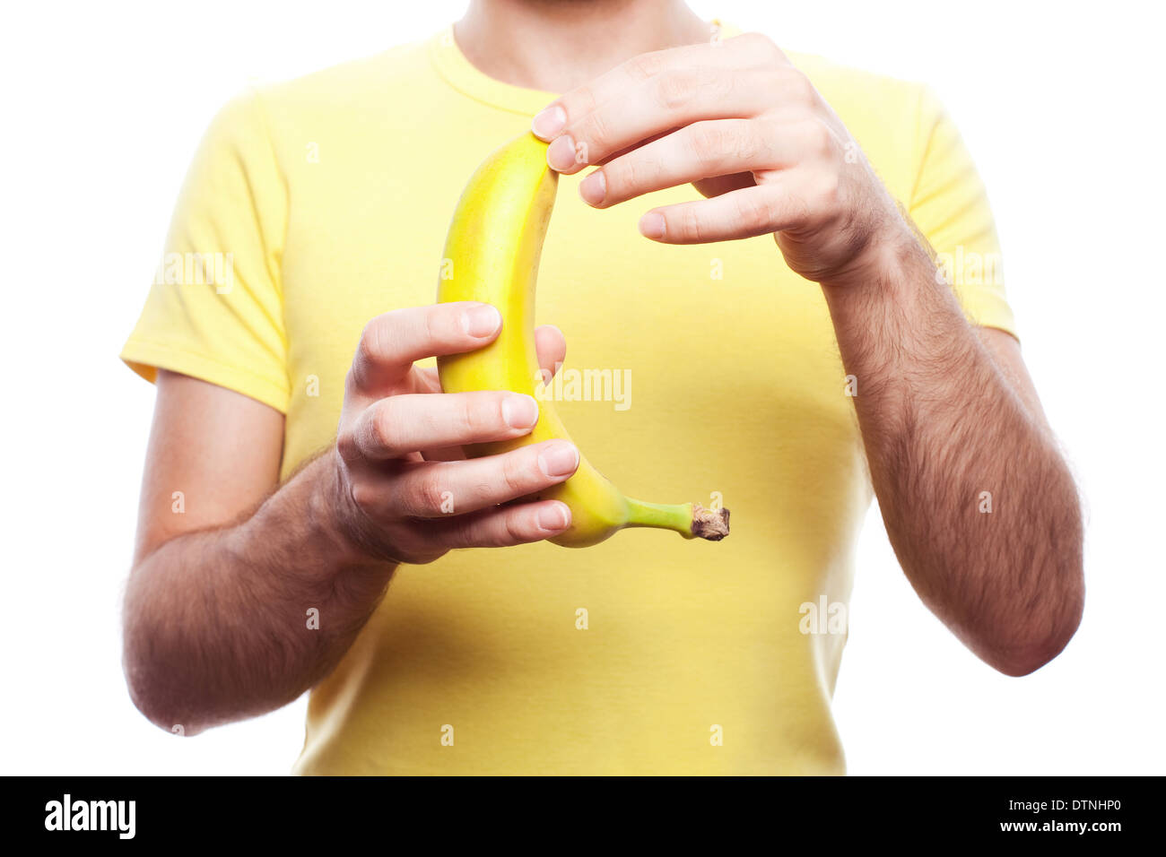 Guy holding et l'ouverture de banane jaune sur fond blanc. studio shot. Photo Stock
