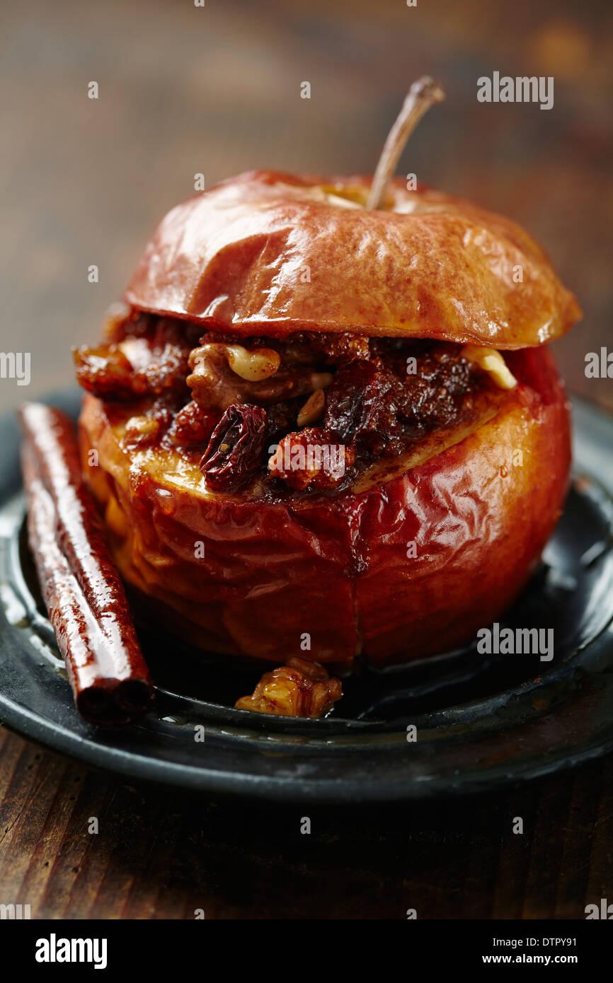 Pomme au four à la cannelle, le sucre brun, le beurre, les noix et les raisins secs Photo Stock