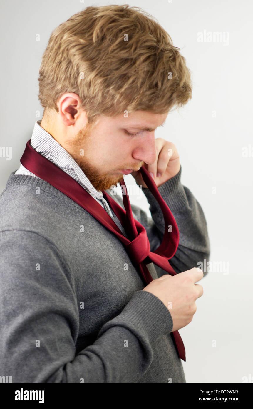 Jeune homme attachant une cravate rouge autour du cou. Photo Stock