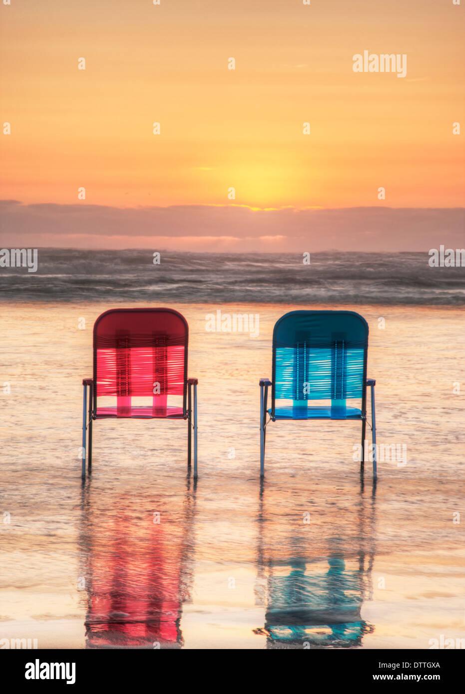 Les chaises de parterre en vagues sur la plage au coucher du soleil Photo Stock