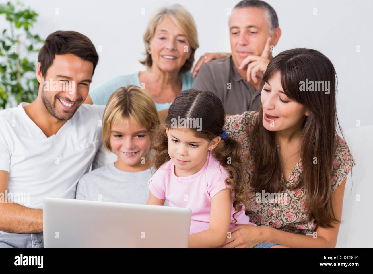 Smiling family regarder quelque chose sur l'ordinateur portable Photo Stock