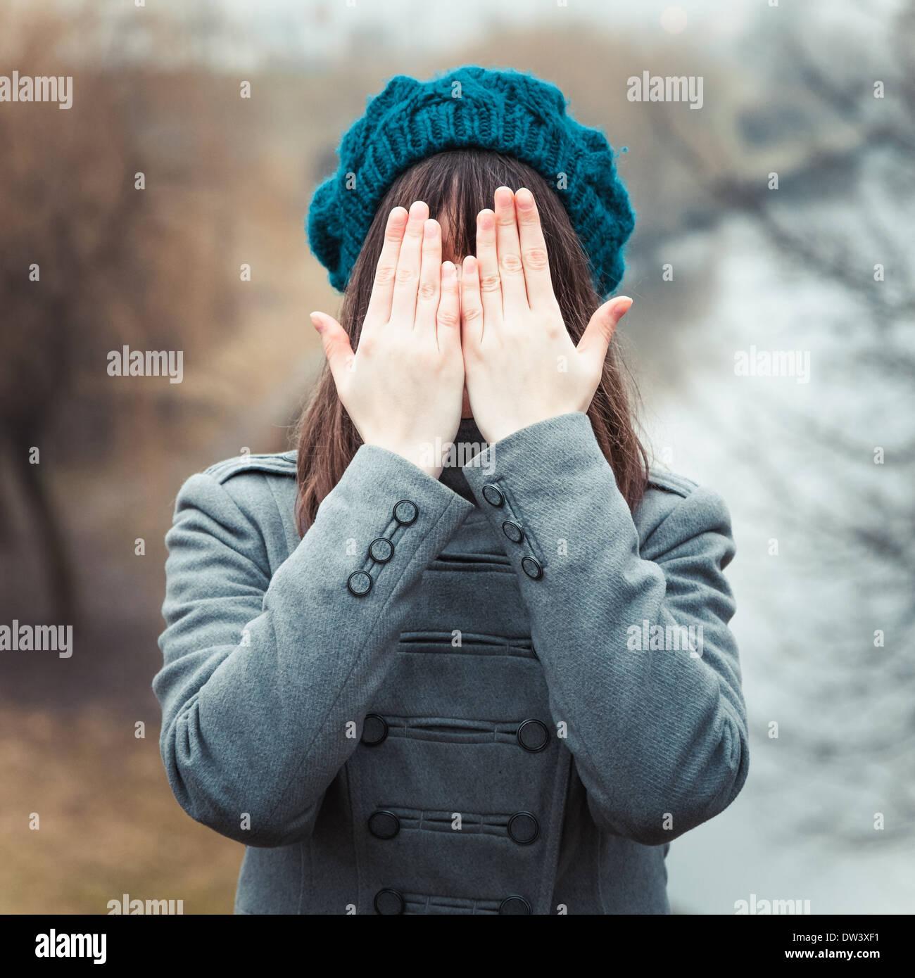 Jeune jolie fille avec les mains sur les yeux à l'extérieur Photo Stock
