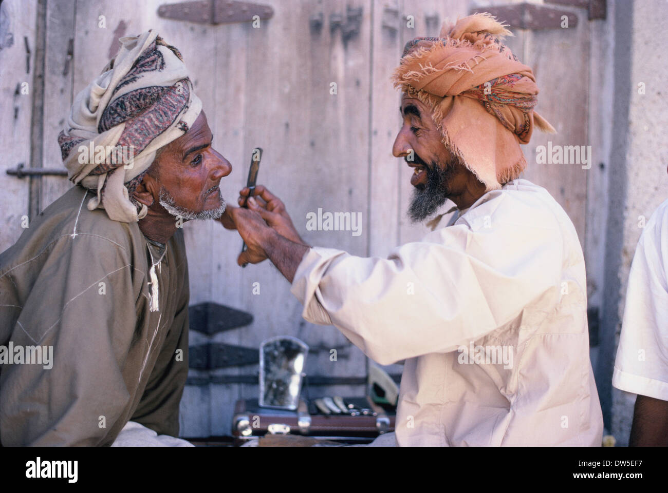 Coiffure omanais et client, Muscat, 1969. La culture traditionnelle omanaise et robe. Photo Stock