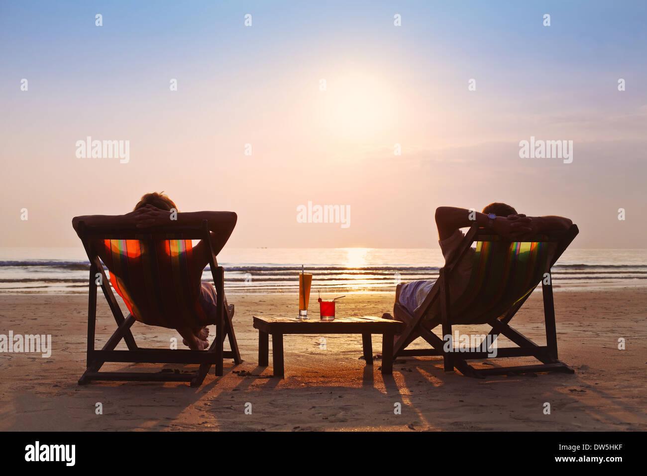 Couple heureux admirer le coucher du soleil sur la plage Photo Stock