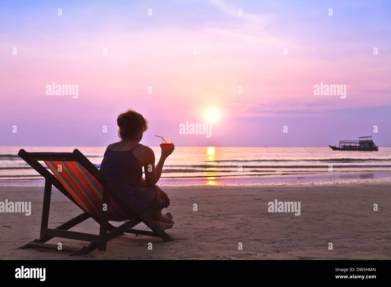 Femme d'âge moyen avec cocktail admirer le coucher du soleil sur la plage Photo Stock