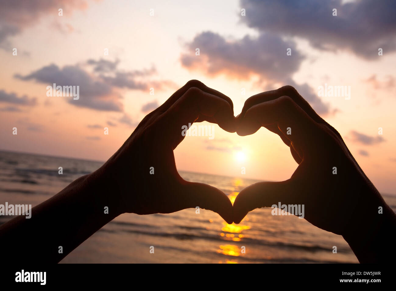 Coeur de mains de couple sur la plage Photo Stock