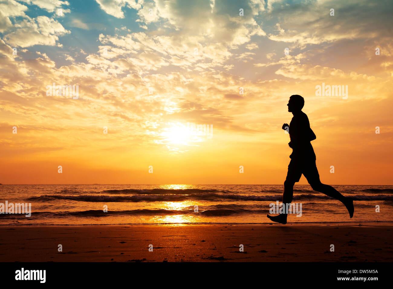 Silhouette d'homme qui court sur la plage au coucher du soleil Photo Stock
