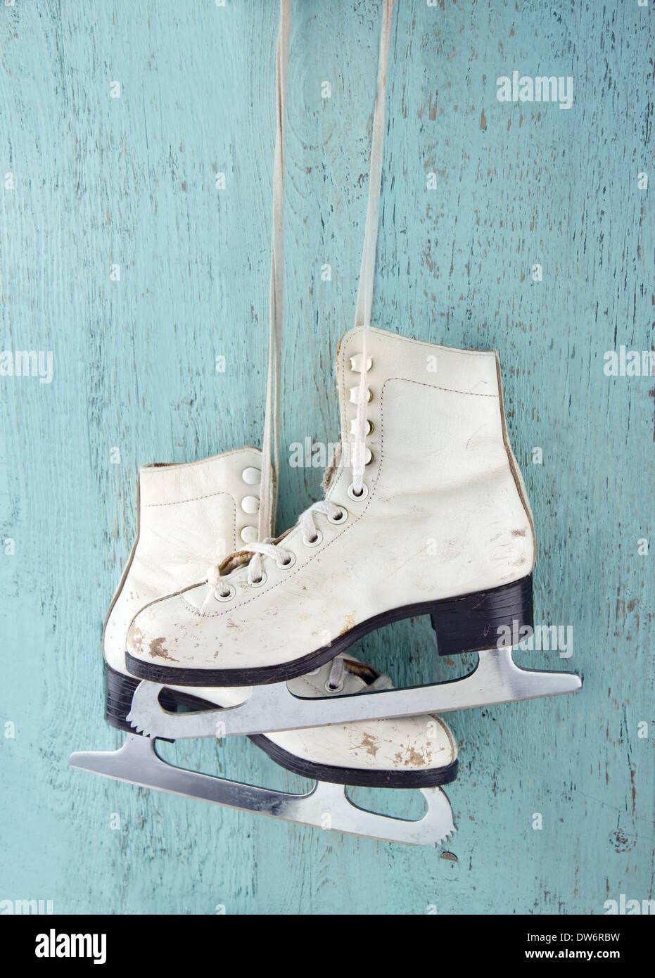 Paire de patins à glace pour femmes blanc sur bleu vintage background - féminin concept sports d'hiver Photo Stock