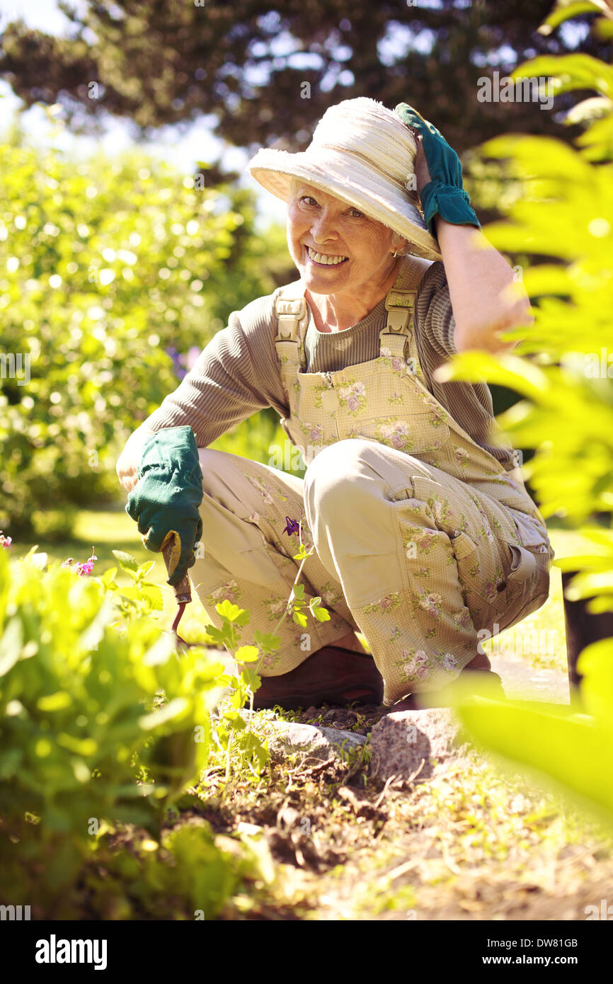 Happy woman gardening in backyard looking at camera smiling Photo Stock