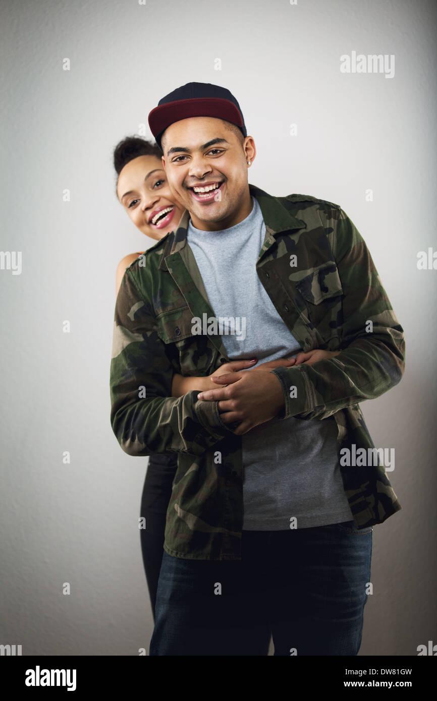 Cheerful hispanic couple jeune ensemble sur fond gris. Jeune femme avec son beau petit ami smiling at camera. Photo Stock