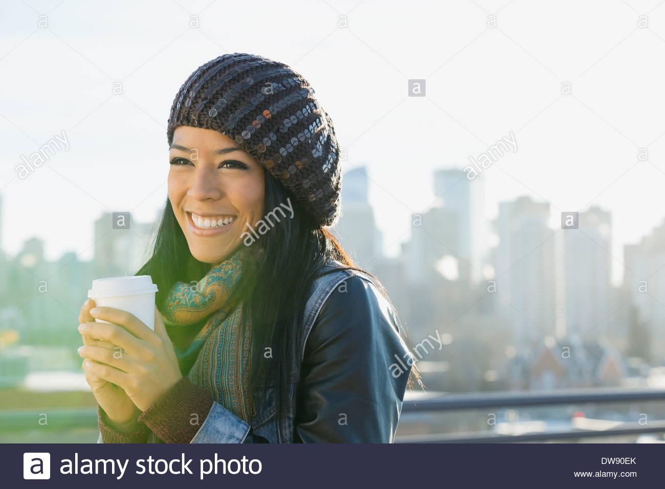 Femme tenant une tasse à café jetable en plein air Photo Stock
