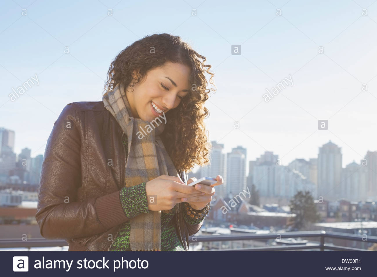 Smiling woman using smart phone sur patio contre cityscape Photo Stock