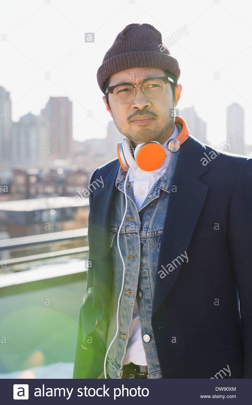 L'homme réfléchi avec des écouteurs debout sur patio Photo Stock