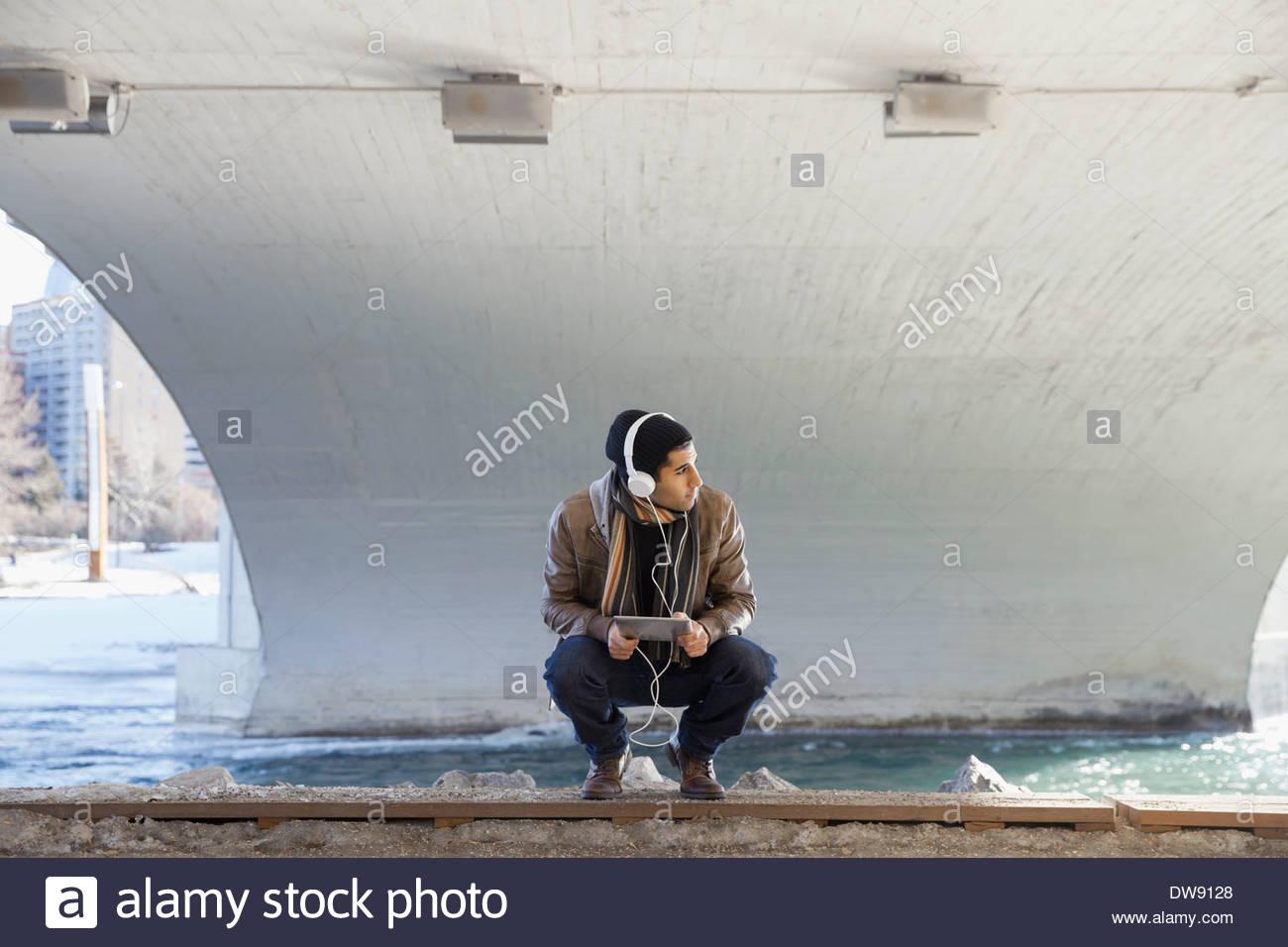L'homme accroupi en plein air avec tablette numérique et écouteurs Photo Stock