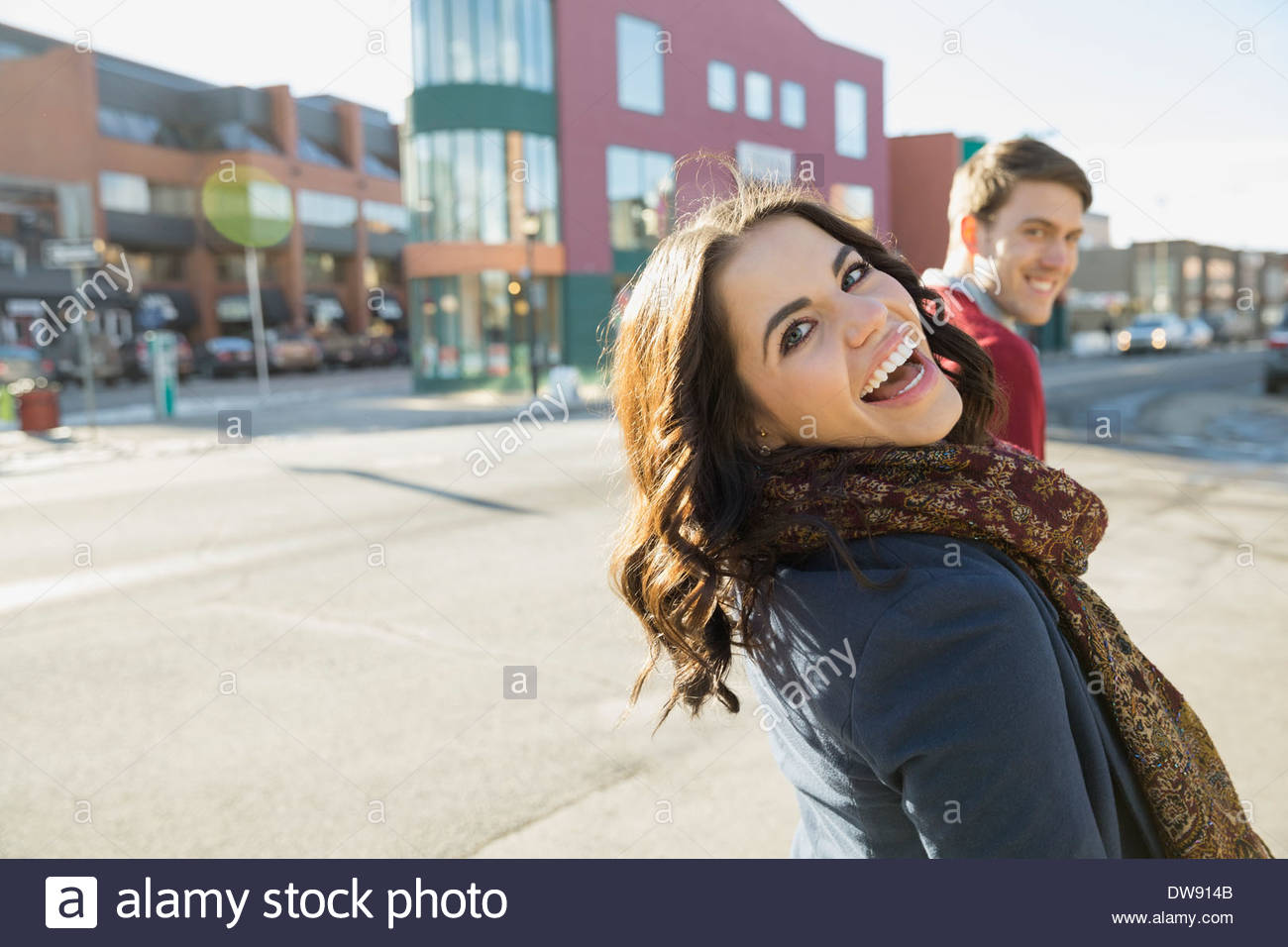 Cheerful woman looking back on city street Photo Stock