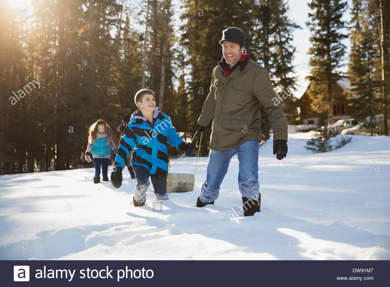 Père et fils en tirant dans la neige luge Photo Stock